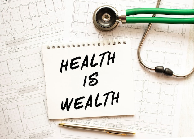 Stetoskop z kardiogramem i notes z napisem zdrowie to bogactwo. pojęcie opieki zdrowotnej.