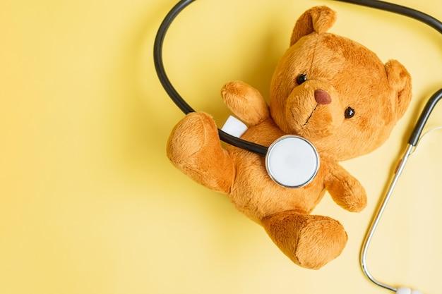 Stetoskop z lalką bear na żółtym tle do wspierania życia i choroby dziecka. wrzesień miesiąc świadomości raka u dzieci, koncepcja opieki zdrowotnej i ubezpieczenia na życie