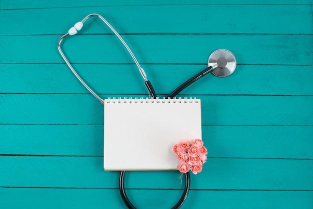 Stetoskop z notatnikiem i małymi różowymi kwiatkami