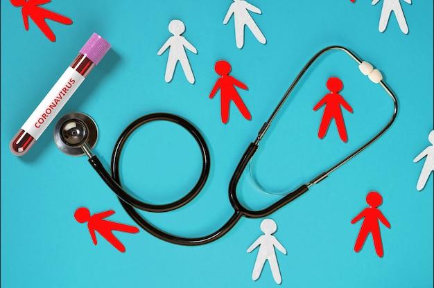 Stetoskop z papierowymi mężczyznami i probówką z próbką krwi