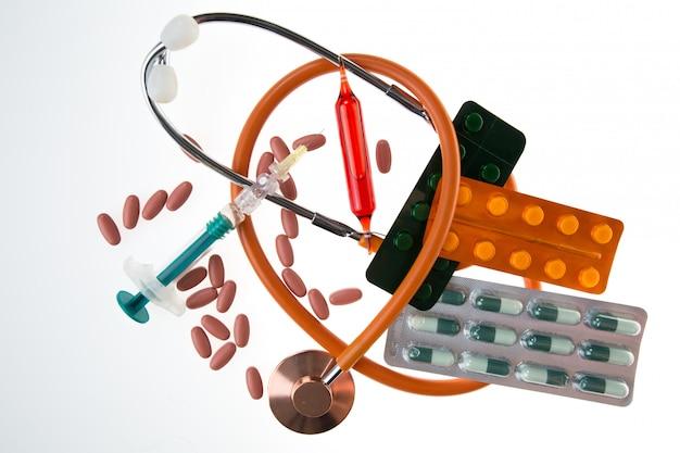 Stetoskop z różnymi elementami farmaceutycznymi na białym tle