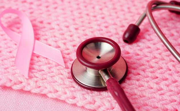 Stetoskop z różową wstążką i na różowym tle z tkaniny koncepcja świadomości raka piersi