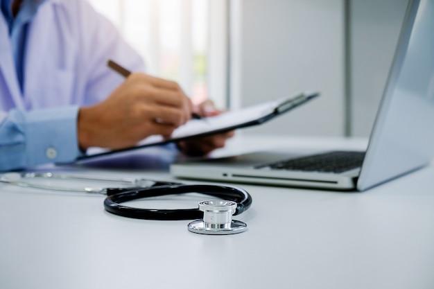 Stetoskop z schowka i laptopa na biurko, lekarz pracuje w szpitalu pisania recepty, opieki zdrowotnej i koncepcji medycznej, wyniki testów w tle, vintage kolor, selektywna fokus.