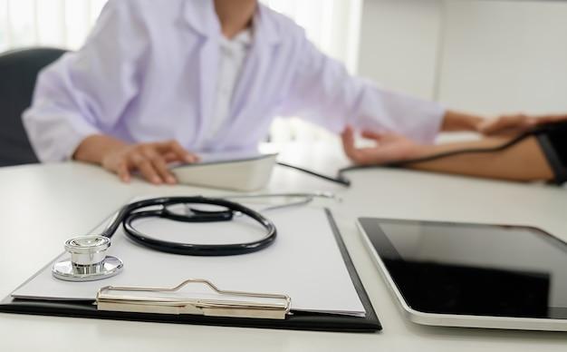 Stetoskop z schowka i laptopa na biurko, lekarz pracuje w szpitalu pisanie recepty, opieki zdrowotnej i koncepcji medycznej, wyniki testów w tle