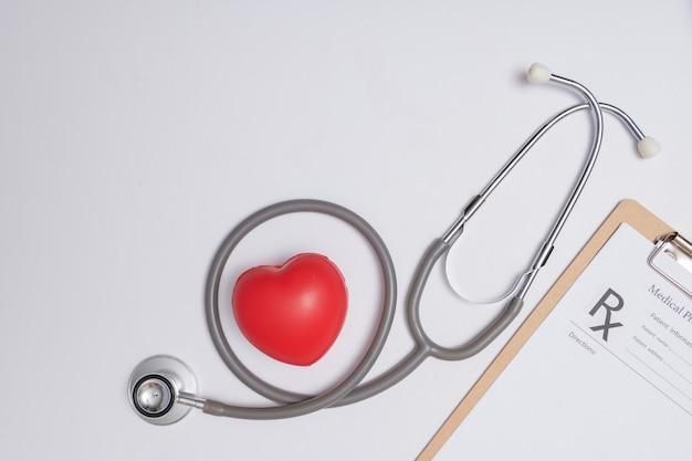 Stetoskop z sercem. stetoskop i czerwone serce na drewnianym stole. koncepcja ubezpieczenia na życie szpitala. pomysł na światowy dzień zdrowia serca. koncepcja medycyny lub farmacji. pusty formularz medyczny gotowy do użycia.