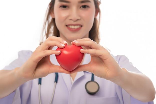 Stetoskop z sercem w lekarek rękach odizolowywać na białym zakończeniu, copyspace, opieka zdrowotna.