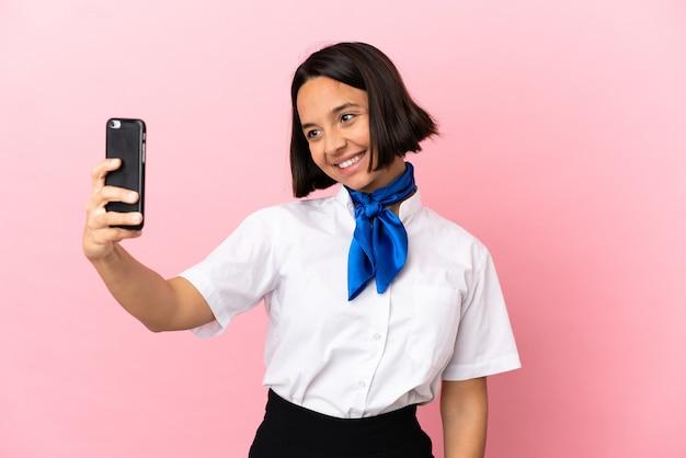 Stewardesa samolotu na białym tle robi selfie