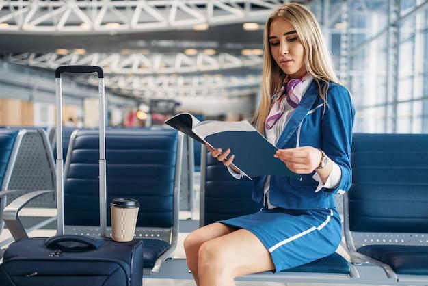Stewardessa czyta magazyn w poczekalni na lotnisku