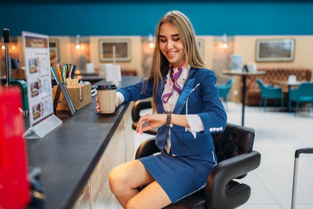 Stewardessa pije kawę w kawiarni na lotnisku