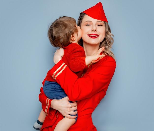 Stewardessa w czerwonym mundurze z dzieckiem na rękach