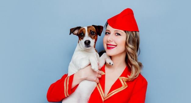 Stewardessa w czerwonym mundurze z psem