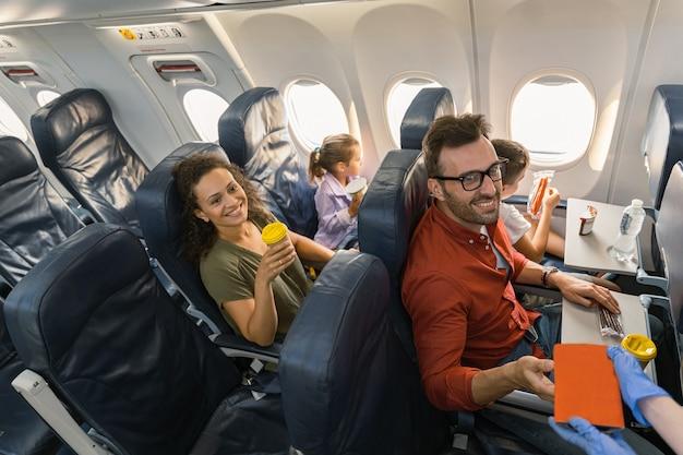Stewardessa w rękawiczkach ochronnych wręczająca pasażerowi pudełko na lunch