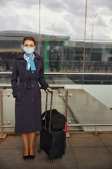 Stewardessy z bagażem stojące w pobliżu nowoczesnego lotniska. kobieta nosić mundur i maskę medyczną i patrząc na kamery. cywilne lotnictwo komercyjne. koncepcja podróży lotniczych