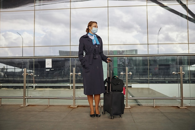 Stewardessy z bagażem stojące w pobliżu nowoczesnego lotniska. młoda kobieta nosić mundur i maskę medyczną. cywilne lotnictwo komercyjne. koncepcja podróży lotniczych