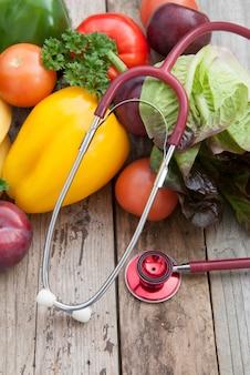 Sthetoscope i świeże kolorowe warzywa składniki fo wegańskie i zdrowe gotowanie sałatki na rustykalne, widok z góry,. copyspace.