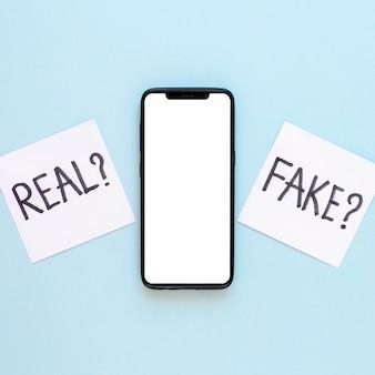 Sticy notatki z fałszywymi wiadomościami obok telefonu