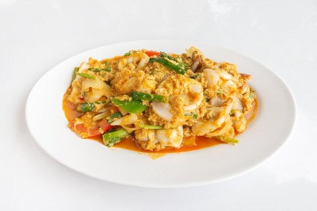 Stir-fried squid z curry w proszku na białym stole tajskie jedzenie lokalne, widok z góry close-up.