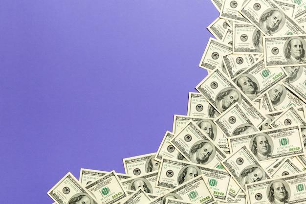 Sto banknotów dolarowych na fioletowym widoku z góry,
