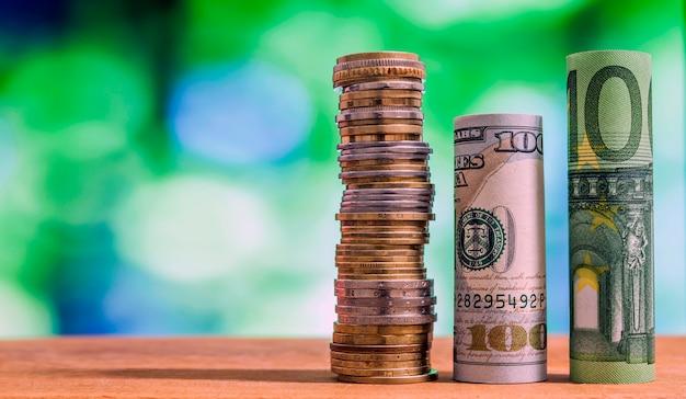 Sto banknotów walcowanych w euro i sto dolarów amerykańskich, z monetami i centami euro