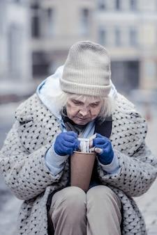 Sto. smutna biedna kobieta patrząc na pieniądze siedząc przy papierowym kubku