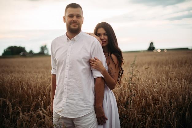 Stock photo portret brodaty chłopaka przytulanie jego wspaniała dziewczyna zarówno w białe ubranie przytulanie w polu pszenicy. piękne pole pszenicy w tle.