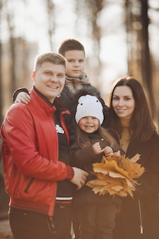 Stock photo portret pięknej wesołej rodziny z synem i córką, trzymając kiść żółtych liści i śmiejąc się w aparacie. wesoła rodzina kaukaska razem w słonecznym jesiennym parku.