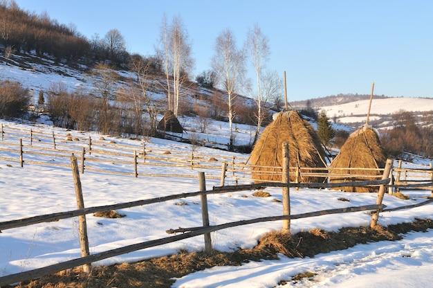 Stogi siana i ogrodzenie z drewna, zimowy krajobraz