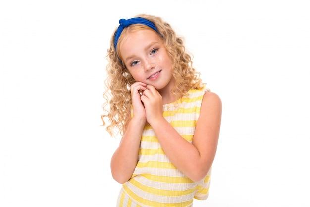 Stoi mała dziewczynka z czerwonymi włosami w letnim garniturze w biało-żółte paski z niebieskim bandażem na głowie.