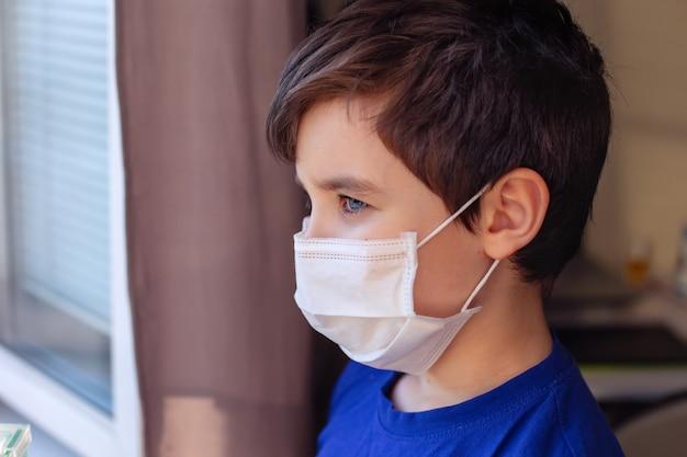 Stoi portret brunetki w niebieskim ubraniu i białej masce medycznej, wygląda przez okno. ścieśniać. skopiuj miejsce