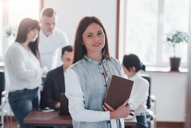 Stoi przed kolegami. grupa ludzi na konferencji biznesowej w nowoczesnej klasie w ciągu dnia