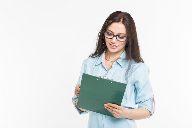 Stoi studentka z zielonym folderem