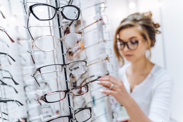 Stoisko modnej elegancji okularów w sklepie. prezentacja z okularami w nowoczesnym sklepie okulistycznym. kobieta w tle. zbliżenie.