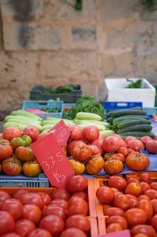 Stoisko z czerwonymi pomidorami i ogórkami w koszach na targu pollensa w palma de mallorca hiszpania