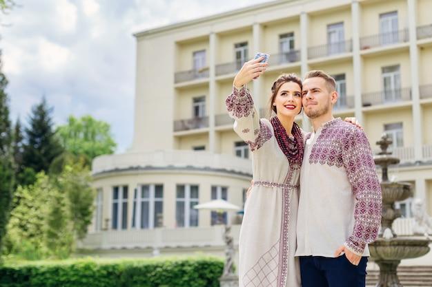 Stoją nowożeńcy w haftowanych ubraniach