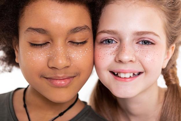 Stojąc blisko. atrakcyjne dzieciaki bez skazy łączące policzki i eksponujące twarze sztucznymi piegami