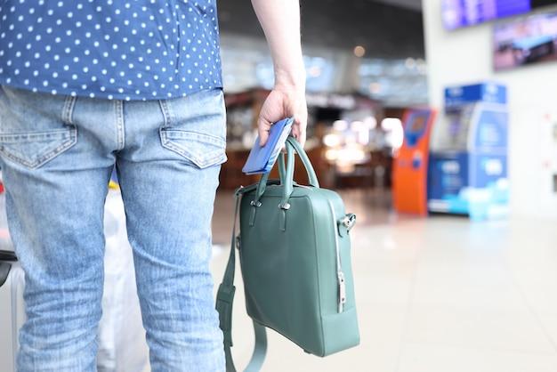Stojąc na lotnisku mężczyzna trzyma w ręku torbę z paszportem i biletami