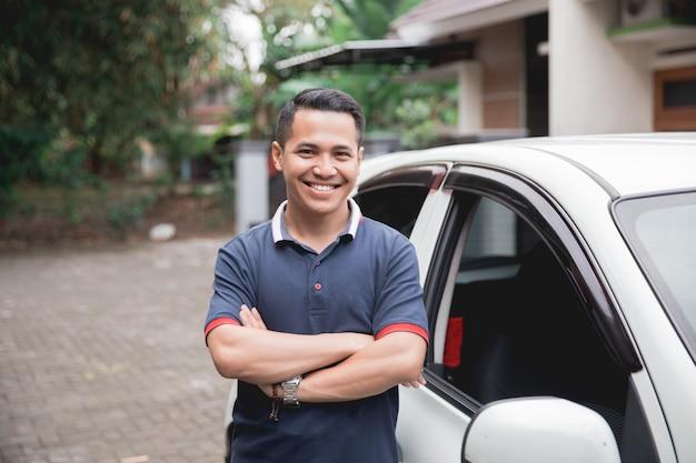 Stojąc przed samochodem. mężczyzna taksówkarz