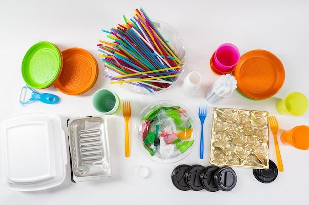 Stojąc razem. kolorowe toksyczne rzeczy wykonane ze szkodliwego plastiku stojące na białej powierzchni jako przykłady naszej chaotycznej konsumpcji