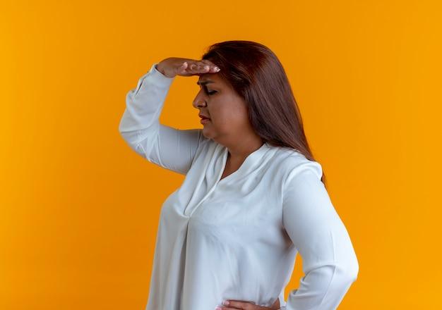 Stojąc w widoku profilu dorywczo kaukaski kobieta w średnim wieku patrząc na odległość ręką odizolowaną na żółtej ścianie