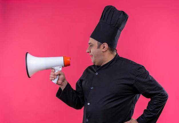 Stojąc w widoku profilu mężczyzna w średnim wieku kucharz w mundurze szefa kuchni mówi przez głośnik