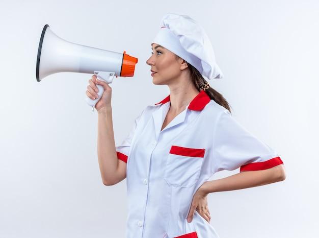 Stojąc w widoku profilu młoda kobieta kucharz ubrana w mundur szefa kuchni mówi przez głośnik, kładąc rękę na biodrze na białym tle na białej ścianie