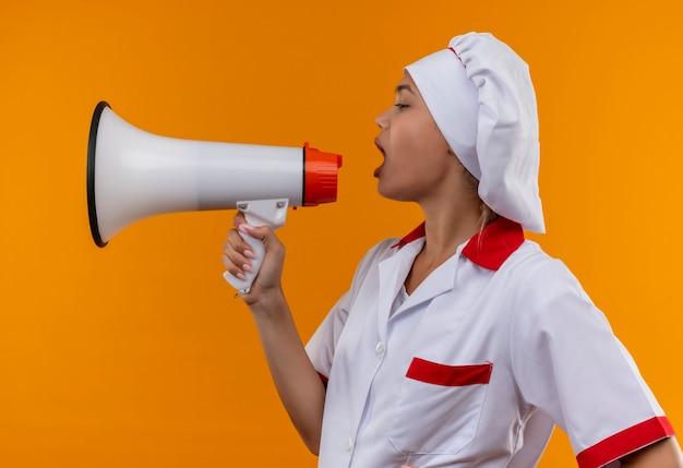 Stojąc w widoku profilu młoda kobieta kucharz ubrana w mundur szefa kuchni mówić przez głośnik na odosobnionym pomarańczowym tle