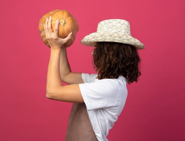 Stojąc w widoku profilu młoda kobieta ogrodnik w mundurze na sobie kapelusz ogrodniczy podnoszący dyni
