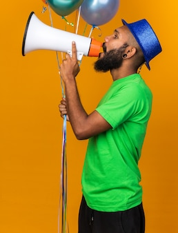 Stojąc w widoku profilu młody afroamerykanin w kapeluszu imprezowym, trzymający balony, mówi przez głośnik