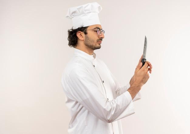 Stojąc w widoku profilu młody mężczyzna kucharz ubrany w mundur szefa kuchni i okulary, trzymając i patrząc na nóż na białym tle na białej ścianie