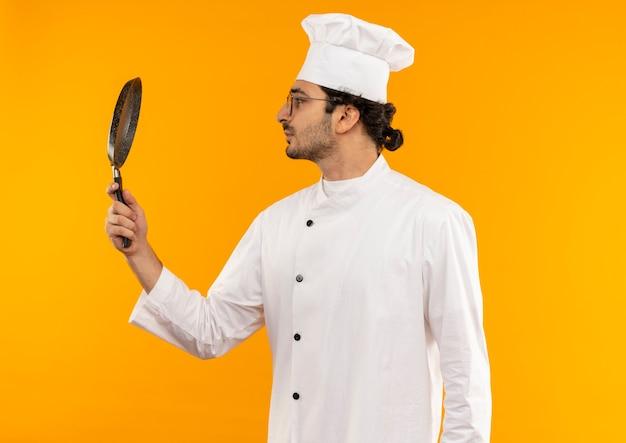 Stojąc w widoku profilu młody mężczyzna kucharz ubrany w mundur szefa kuchni i okulary, trzymając i patrząc na patelnię na białym tle na żółtej ścianie