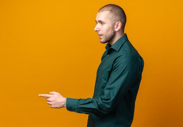 Stojąc w widoku profilu młody przystojny facet ubrany w zieloną koszulę wskazuje z boku