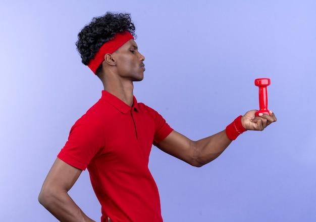 Stojąc w widoku profilu pewnie młody człowiek sportowy noszenia pałąka