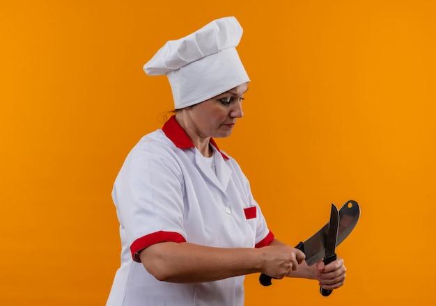 Stojąc w widoku profilu w średnim wieku kobieta kucharz w mundurze szefa kuchni sharpes nóż