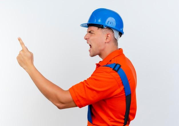 Stojąc w widoku profilu zły młody mężczyzna budowniczy na sobie mundur i kask ochronny wskazuje na bok na białym tle